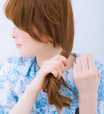 メイクアップミルク(グラマラス)を2プッシュ手のひらに取り、しっかりなじませる。髪全体を手ぐしで左耳下あたりにまとめ、毛束をゆるくたるむように、細いゴムで結ぶ。