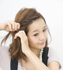 少しずつ毛束を足しながら前髪をねじって右サイドまで持っていったら、毛先をバレッタでとめる。
