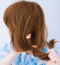 まとめた毛束に、指先で内側から穴を開ける。その穴に毛先を入れこみ、くるっと折り返す。