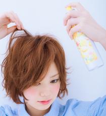 指先で毛束をつまんで、根元にフワフワシューをスプレーする。トップを立ち上げ、表面に動きを出したらできあがり。