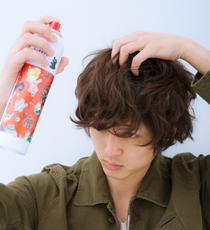 トップの毛束を立ち上げるようにつかんで、根元に向けてカチカチシューをスプレーする。毛先も指先でつまみながらスプレーする。