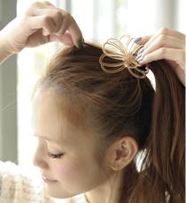 結んだ部分を押さえながら、トップの髪をふんわりと引き出す。
