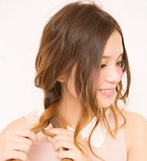 髪全体を右サイドへ集め、ゆるい質感の三つ編みにする。顔まわりの髪は両サイドともナチュラルに残しておく。