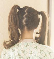 髪を2つに分け、高めの位置でツインテールに。あえて左右で高さを変えてアシンメトリーにするのがポイント。