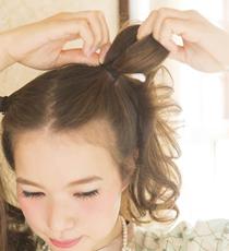 ツインテールのゴムの結び目から毛束を引き出し、ゆるいループを作る。毛先はおくれ毛として残しておく。