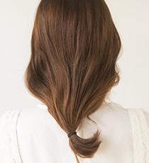 全体をバックでひとつにまとめ、毛先をゴムでゆるく結ぶ。