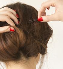 折り畳んだ毛束をアメピンで数カ所留める。このとき、形やバランスを見ながら留めていくこと。