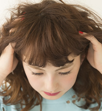 髪の内側に手を入れ、なじませたあと、くしゅくしゅっともみ込んでカールをほぐす。