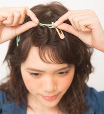 前髪を薄めに取り、ねじってポンパドールにしてピンで留める。
