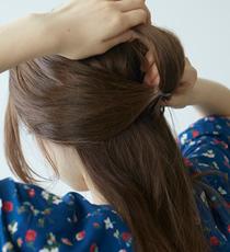 後頭部の厚み半分くらいの髪を分け取り、上部をたるませるぐらいゆるめに縛り土台を作ります。