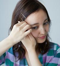根元から前髪にかけてのストレートな髪はタイトになでつけ、ヘアピンで留めて額を出します。