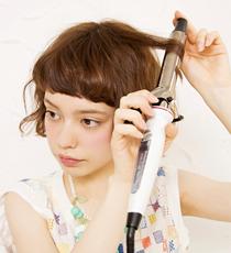 26㎜アイロンを使い、中間から根元まで髪を巻き込む。その後毛先に向かってアイロンをスルーさせる。