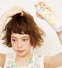 ウェーブジュレを手のひらにのばし、毛先から髪を持ち上げるように揉み込む。その後トップの髪を根元からつまんでフワフワシューをオン。髪全体の根元にも、空気感を与えるように吹きかけて。