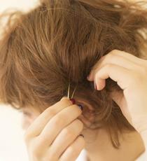 サイドや襟足から毛束をざっくり取ってねじり、毛先を残してピンで留める。これを5~6回繰り返し、すべての髪をねじり上げていく。