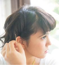 左右各サイドの毛をねじり、耳後ろでピンで留める。