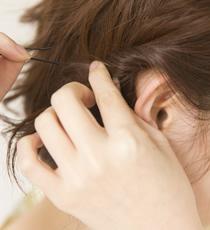 顔まわりをスッキリと見せるため、耳前の毛束をくるくるっとねじって、耳うしろでアメピンで留める。
