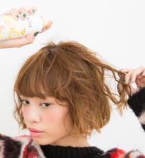 フワフワシューを全体にスプレーして固める。 サイドに残したい毛束だけ残し、残りは耳にかけてからイヤーマフを付けるのがポイント。