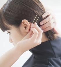 サイドをピタッとタイトに押さえるため、顔まわりの髪を耳にかけたあと、低めの位置でピンで留めて。ゴールドのピンを2本使いするとおしゃれ。