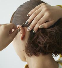 全体の1/2ぐらいまでパーマヘアを手ぐしでストレートになでつけたら、ゴールドのシンプルなヘアピンで留めています。