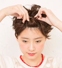 両黒目の中間の幅を目安にして前髪を取り、2回転ねじる。毛束を前へ押し出して立体感をつけ、ピンをクロスして留める。