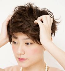 髪をにぎるようにしてワックスを揉み込む。その後9:1パートにして後ろからフロントへ髪を流す。トップをつまみ、根元を立ち上げて。