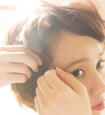 サイドの髪を上下で2つに分け、それぞれ毛束をクルクルねじってピンで留める。