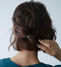 アイロンで巻いた後、手のひらにをピンポン玉2個分出し、泡をつぶしながら髪全体になじませた後、右サイドから後頭部の髪をラフに分け取り、センターに寄せてゴムで縛り土台を作ります。